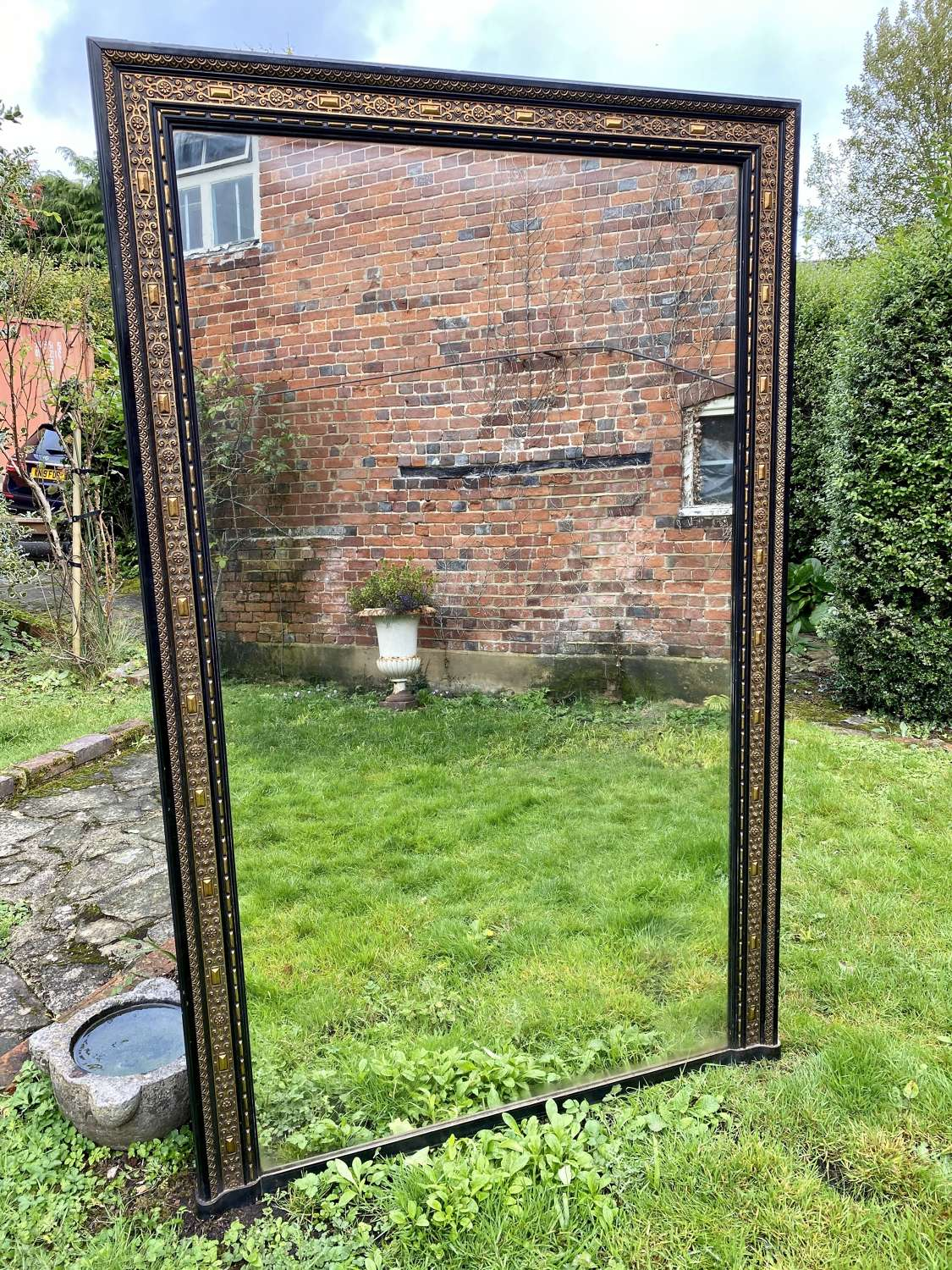 Very large ebonised and gilt mirror