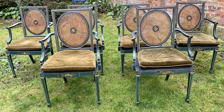 Six painted and caned dining chairs